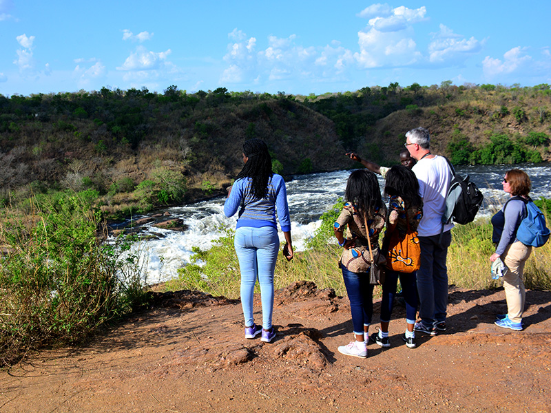 Tourists on the edge of the Nile River at Murchison Falls in Uganda